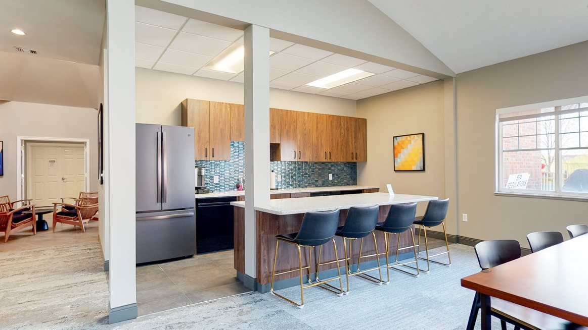 Community clubhouse kitchen with refrigerator and island seating for resident use in the clubhouse at The Northbrook Apartments