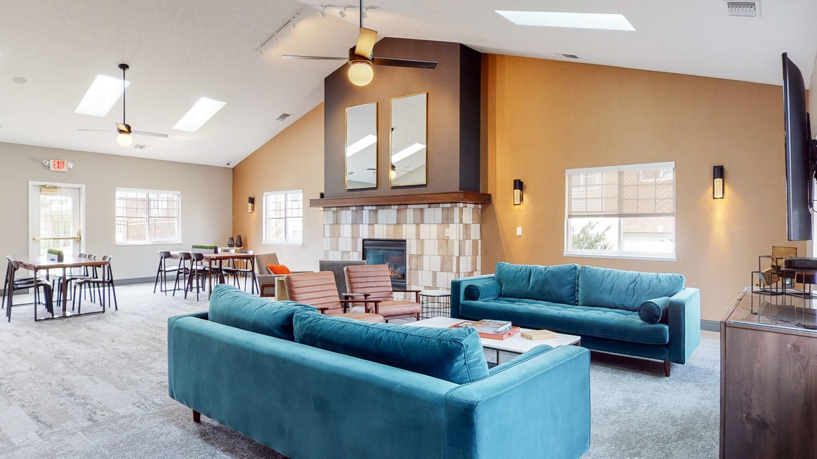 Spacious clubhouse with vaulted ceiling, natural light, fireplace and sitting areas at the Northbrook Apartments