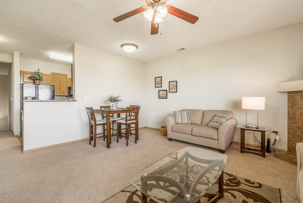 Interiors-Living room with ceiling fan and opening to kitchen at Stone Ridge townhomes in south Lincoln NE