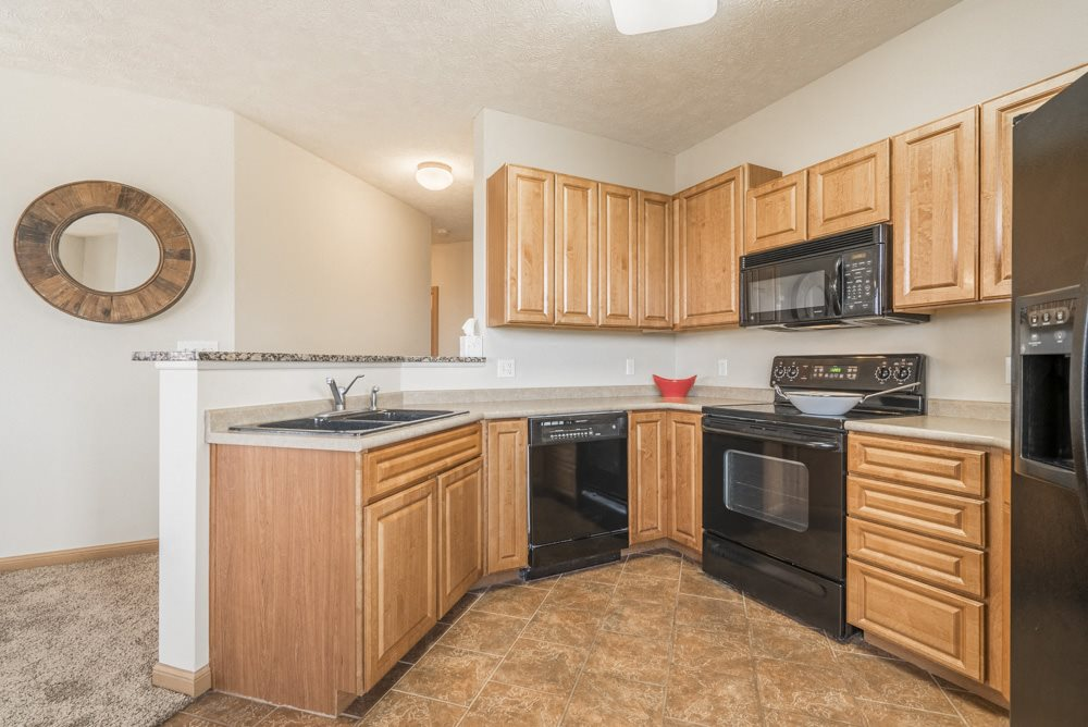 Interiors-Large kitchen with black appliances at Stone Ridge Estates townhomes in South Lincoln