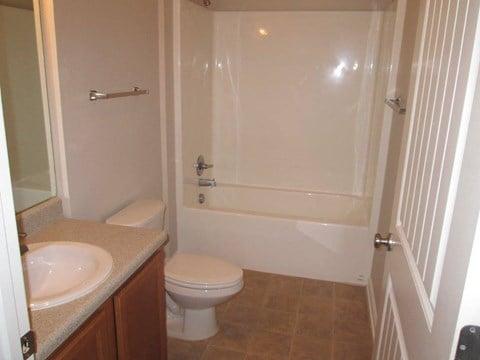 large bathroom with tub, toilet, and bathroom