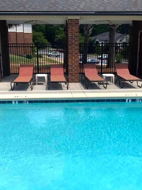 lounge furniture beside sparkling pool