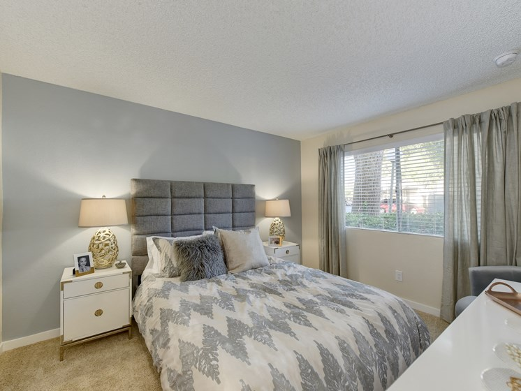 Bedroom with Mattress with Gray/White Comforter, Carpet, White Bedside Dresser with Lamp and Windows