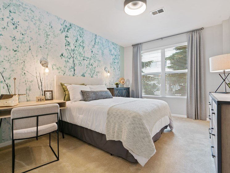 Bedroom layout with desk, queen bed, large window, and carpeting