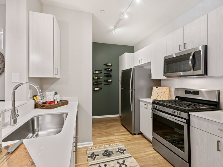View of kitchen with plank flooring, gas stove, microwave, and fridge with a wall decor that holds wine