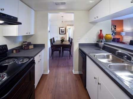 Updated galley kitchen with black appliances   L'Estancia Apartments