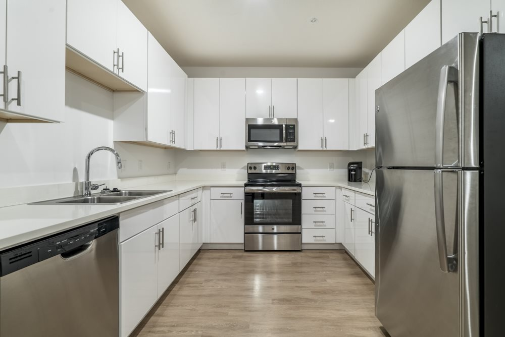 Contemporary kitchen with white cabinetry, quartz countertops and stainless steel appliances at The Conrad