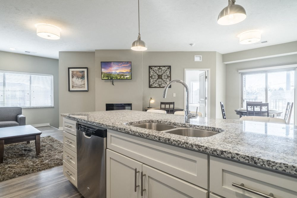 Kitchen with granite counter tops and white cabinets at The Villas at Mahoney Park