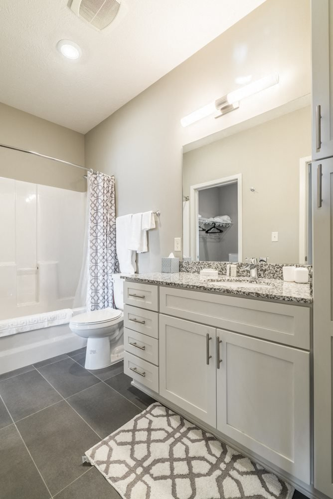 Bathroom with granite counter tops and gray slate flooring at The Villas at Mahoney Park