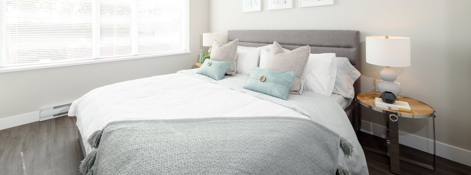 White bed with grey throw blanket and light blue pillows
