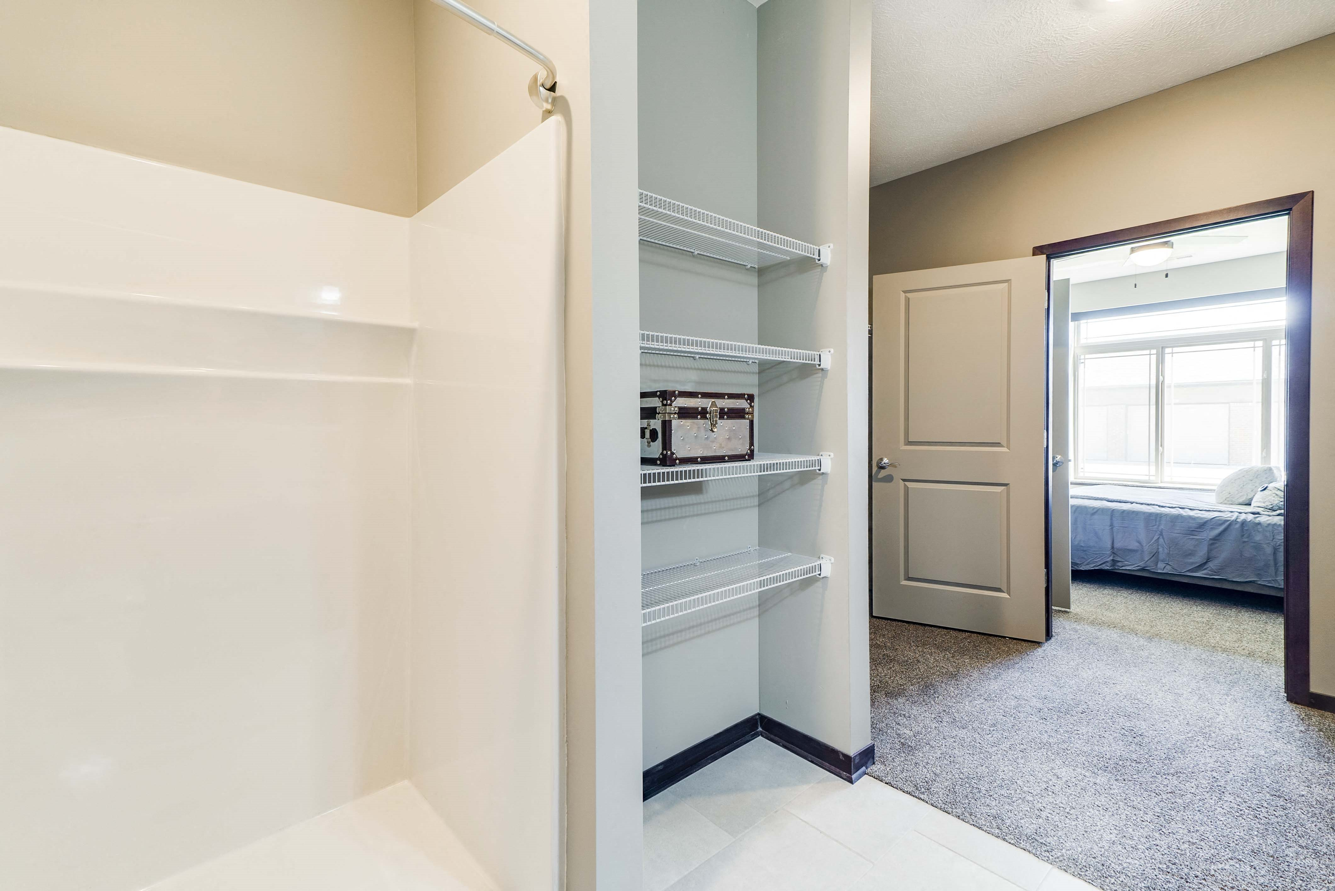 Spacious walk in closet and bathroom with a shower and granite countertops in 2 bedroom apartment for rent at 360 at Jordan West best new apartments West Des Moines IA 50266