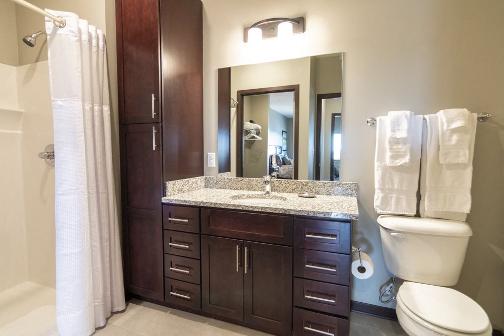 Bathroom with dark cabinetry and light granite countertops at 360 at Jordan West best new apartments West Des Moines IA 50266