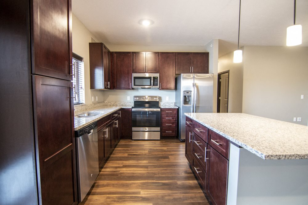 Kitchen with dark cabinetry and island in three-bedroom apartment at 360 at Jordan West best new apartments West Des Moines IA 50266