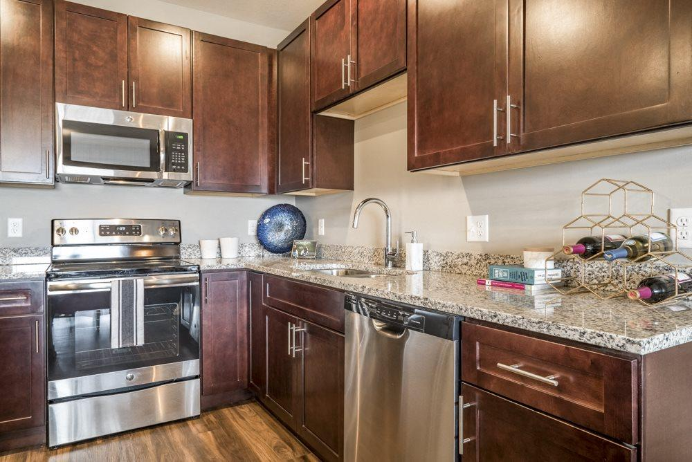 Kitchen featuring light granite countertops, dark cabinetry and stainless-steel appliances at 360 at Jordan West best new apartments West Des Moines IA 50266