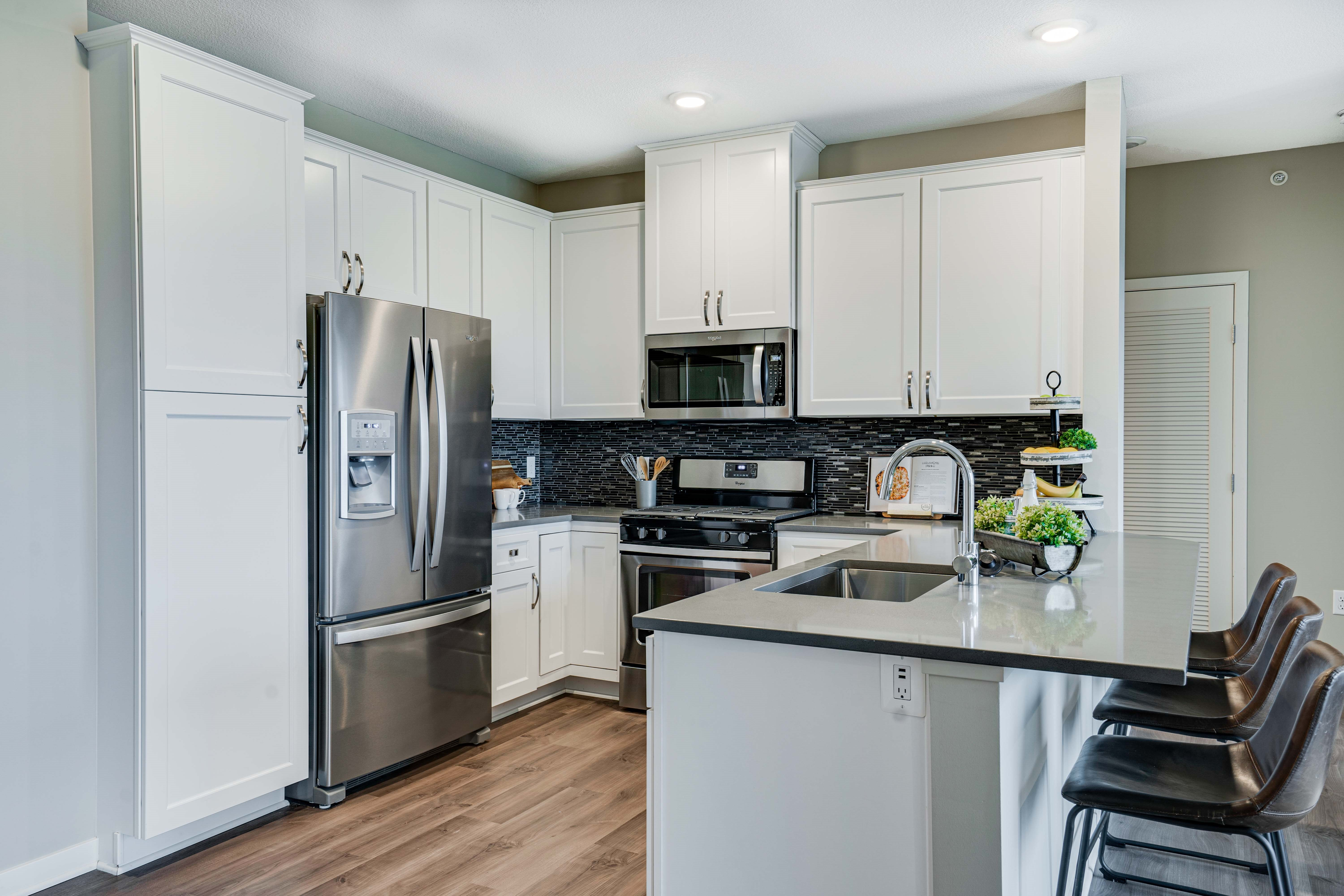 Premium kitchen featuring dark quartz countertops and white cabinetry in a two bedroom penthouse Princeton floor plan