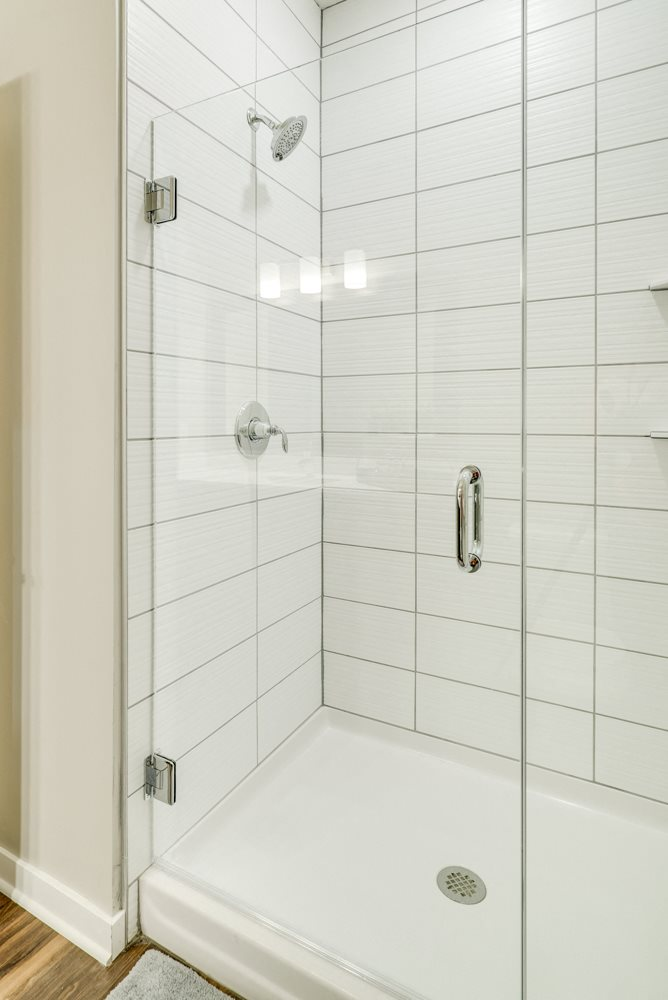 Shower with subway tile and glass doors at Ascend at Woodbury in MN