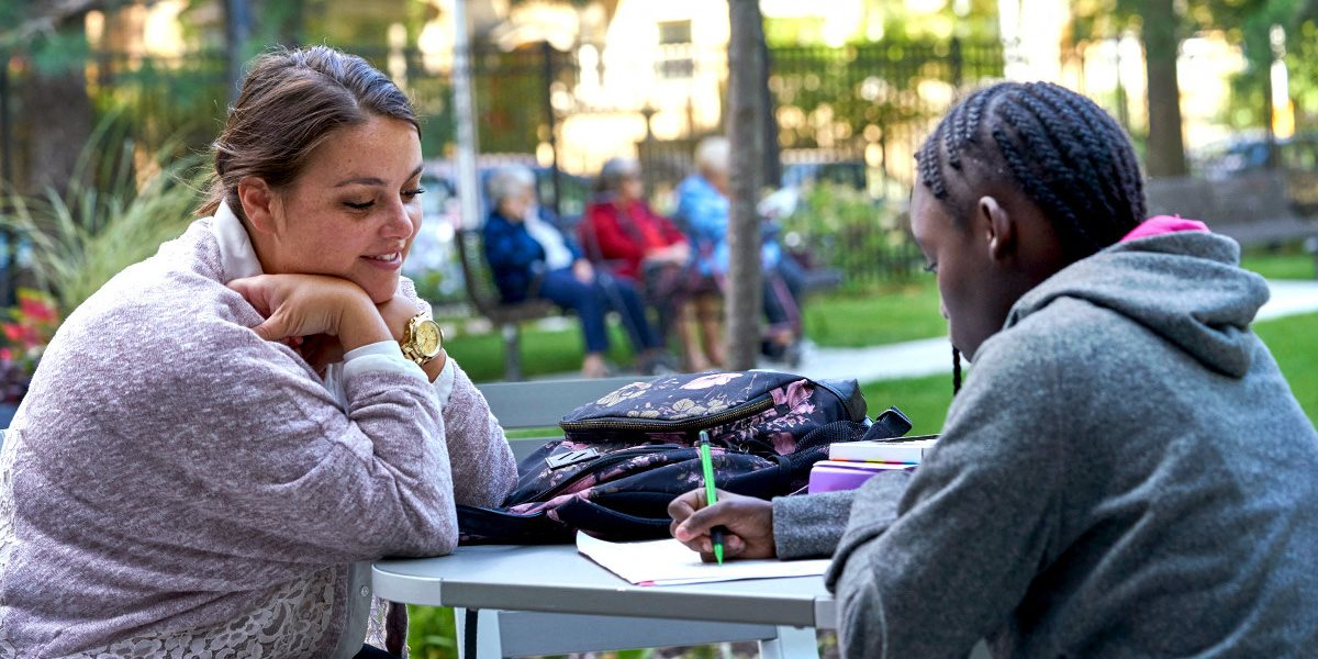 Image of a volunteer helping a resident tackle their homework.