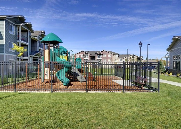 Playground with grass by apt buildings Parker Co Apt Rentals