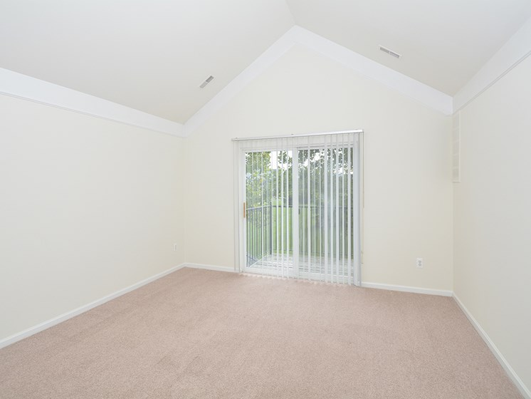 Carpeted Living Room with Vaulted Ceilings and Sliding Glass Patio Door