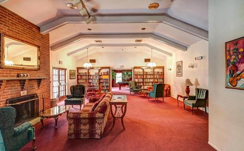 An attractive clubhouse with a billiards room, fireplace, large screen TV and kitchen