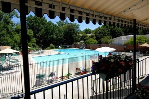 A large outdoor pool with swimming lanes, separate baby pool, on-duty lifeguard, and a sundeck.