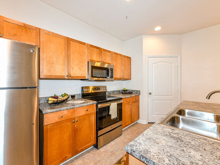 Open Kitchen with Custom Maple Cabinets, Stainless Steel Appliances and Breakfast Bar at Alden Place at South Square Apartments,Durham, NC 27707