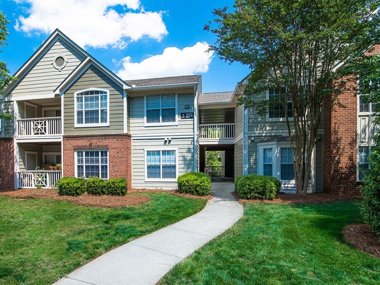 Meticulously maintained grounds with mature trees surround the soft green paint and brick exterior apartment homes at Autumn Park Apartments, Charlotte, NC 28262