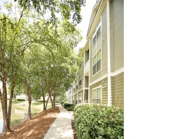Meticulously maintained grounds with mature trees surround the soft green paint and brick exterior apartment homes at Legacy Farm Apartments, Collierville, TN 38017