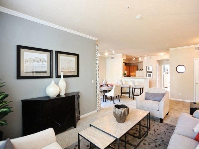 Gorgeous Modern Living Room with Bright White Crown Moulding, Tray Ceilings and Estate Tan Walls plus Wood Burning Fireplaces at Legacy Farm Apartments, Collierville, TN 38017