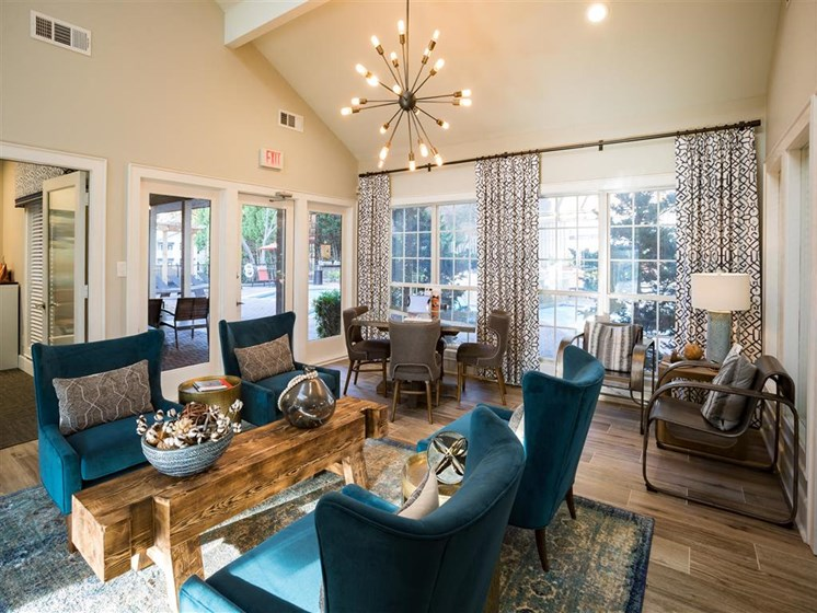 Expertly Designed Spacious Clubhouse with Bright Blue and Wood Accent Decor. Amble Seating and Flat Screen TVs for Residents to Enjoy at Park Summit Apartments, Decatur, GA 30033