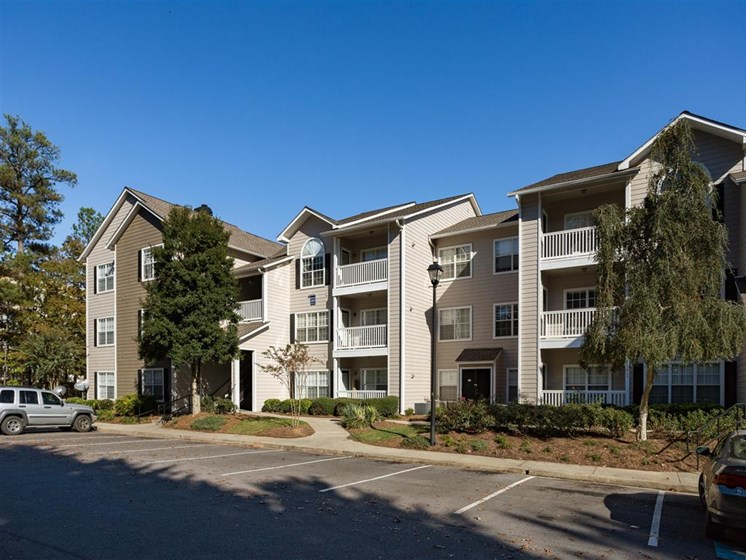 Meticulously maintained grounds with mature trees surround the soft neutral paint and brick exterior apartment homes at Park Summit Apartments, Decatur, GA 30033
