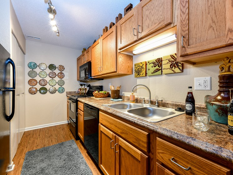 Gourmet Kitchens with G.E. Black Appliances and Maple Raised-Panel Cabinetry at Pointe Royal Townhome Apartments, Overland Park, KS 66213