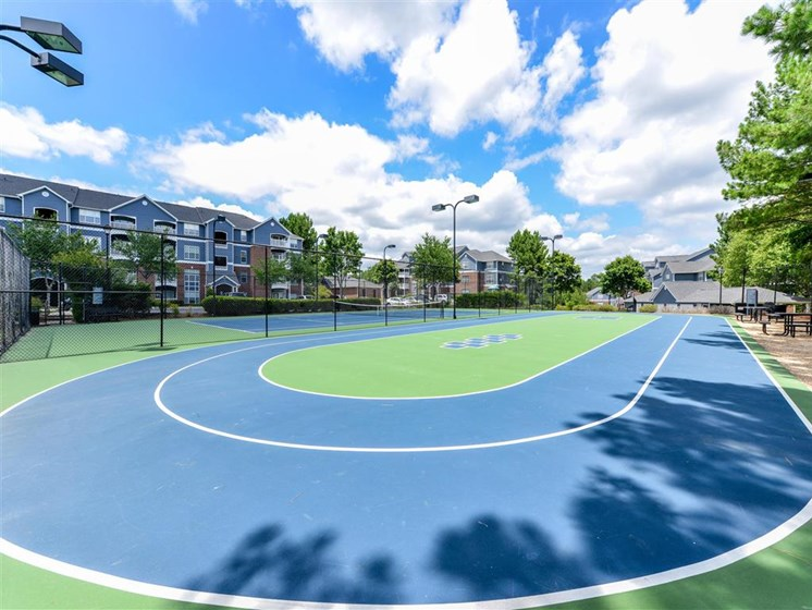 Lighted Tennis Court with Adjacent Sports Court at Sugarloaf Crossing Apartments, Lawrenceville, GA 30046