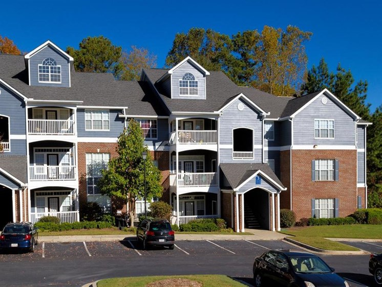 Meticulously maintained grounds with mature trees surround the bright blue paint and brick exterior apartment homes at Sugarloaf Crossing Apartments, Lawrenceville, GA 30046