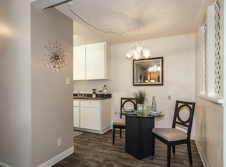 Dining room with dark wood furniture looking into part of kitchen with white cabinets. Abstract art on walls