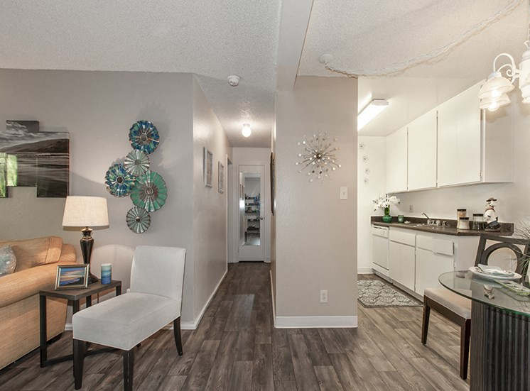 Kitchen with white counters, narrow hallway to bedrooms and part of living room. Beige Living room chair and wall art.
