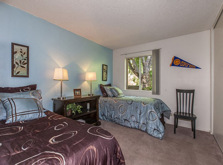 Model bedroom with two twin beds — one brown, one teal — teal wall, lamps, dark furniture, window.