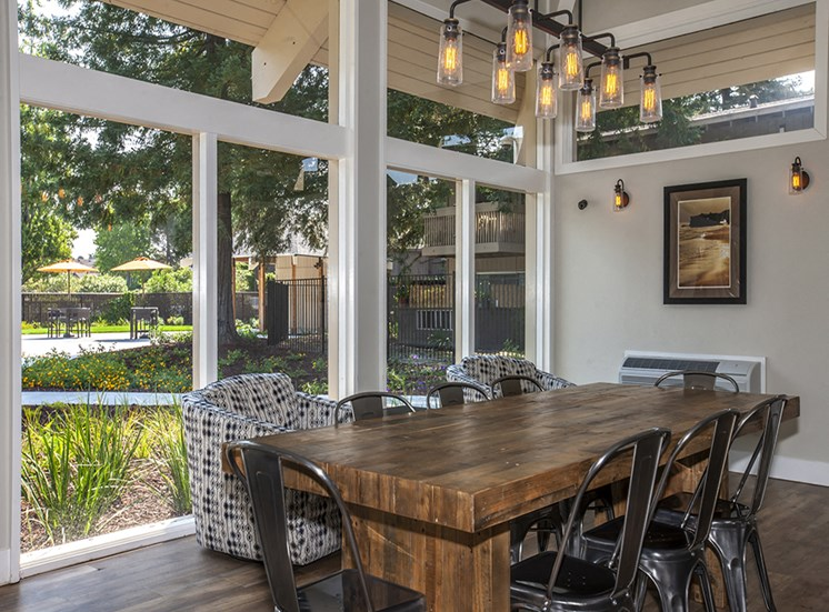 Lounge with wood floors, view of grounds, communal wood table, metal chairs, hip lighting, armchairs