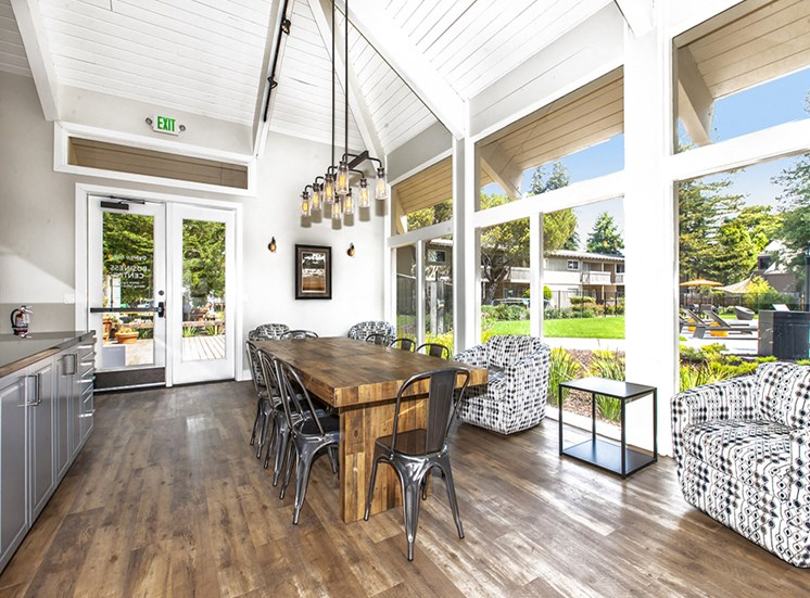 Lounge with view of grounds, communal wood table, metal chairs, cooking counter, hip lighting, armchairs