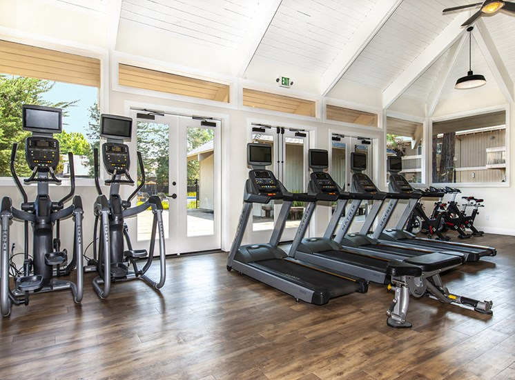 Gym with treadmills/ellipticals with screens in front of windows, Weight bench on wood floors