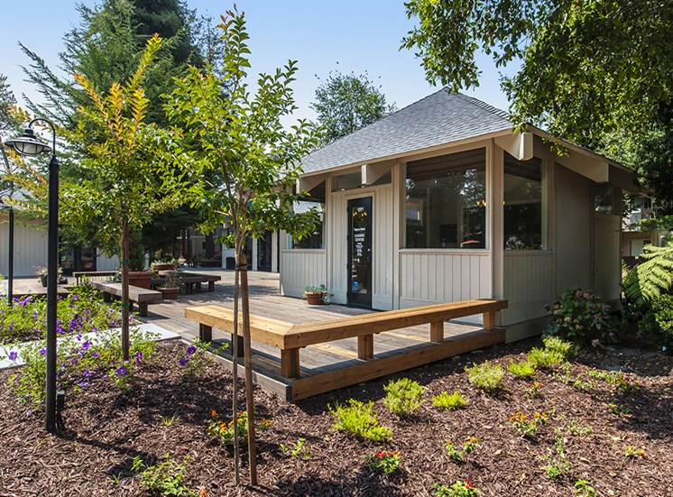 Trees and flowers leading up to lounge building and patio with wooden benches as outdoor seating attached to lounge.