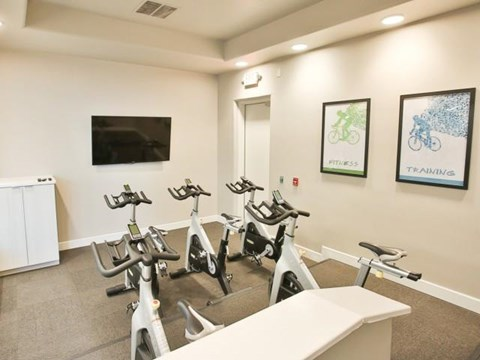 The Highland Apartments Fitness Studio with spin bikes and tv with fitness on demand classes