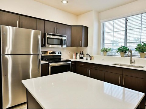 The Highland Kitchen with stainless appliances, dark cabinets, white quartz counters and light faux wood flooring