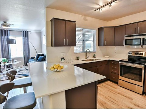 The Highland Apartments kitchen with brown cabinets, stainless appliances and quartz counters