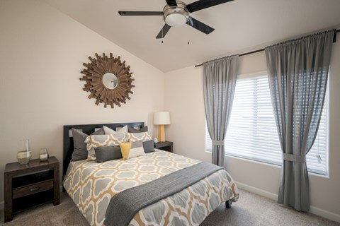 Model bedroom with wall to wall carpet, ceiling fans, queen bed, and large windows