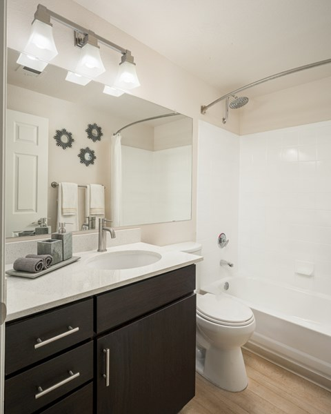 Bathroom with light faux wood floors, brown cabinets, white quartz cabinets and tub/shower