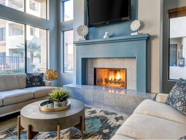 Ingleside Apartments Clubhouse Sitting area with blue fireplace with tv above and beige couches