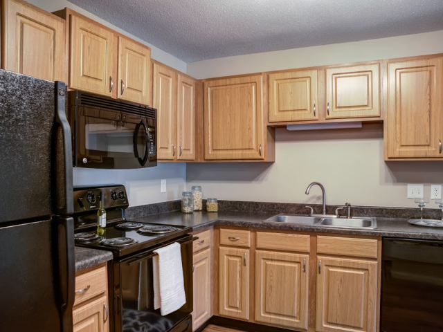 Full Model Kitchen with Frost-free Refrigerator, Black Appliances and Light Wood Cabinetry