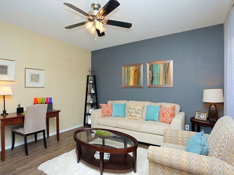 Spacious living room with ceiling fan and wood plank flooring