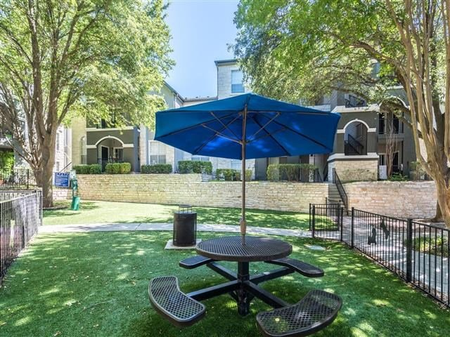 Fenced in dog park with umbrella shaded bench seating